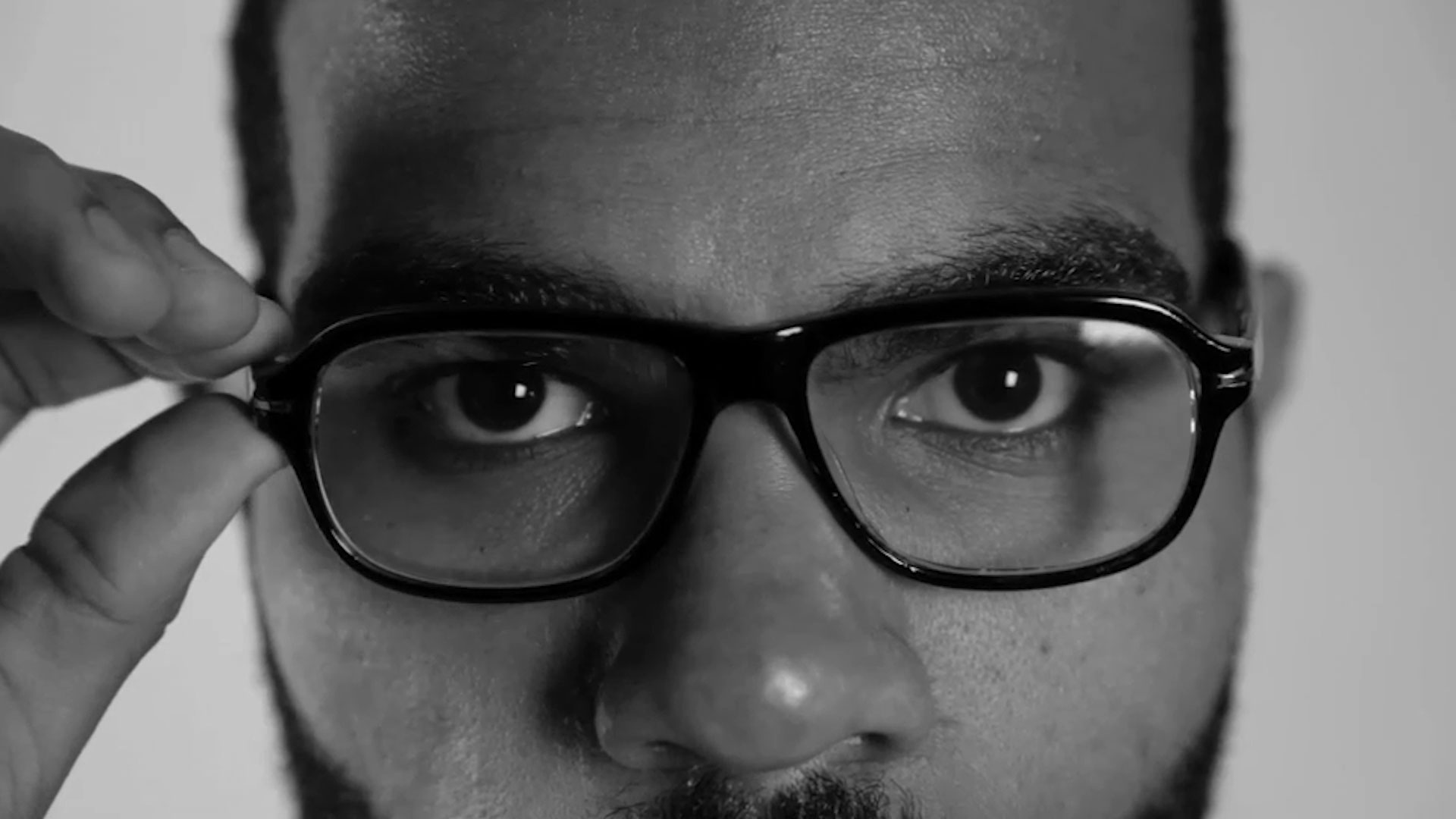 person glasses eyes wearing face man human face indoor looking portrait close black and white staring